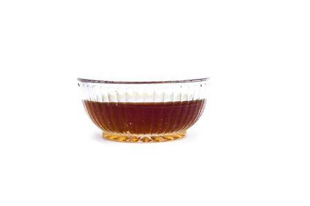 Raw organic fresh honey or nectar isolated on white in a glass bowl.