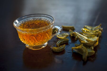 Hot herbal ayurvedic aloe vera tea on wooden surface in  transparent glass cup with entire ingredients with it.Used to build immnue system, To Lower cholesterol levels and many more.