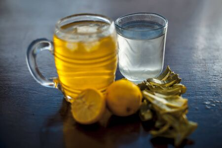Herbal detoxifying aloe vera iced tea in a big transparent glass with entire ingredients which are orange & lemon juice,tea leaves powder,coconut water and honey and aloe vera gel.