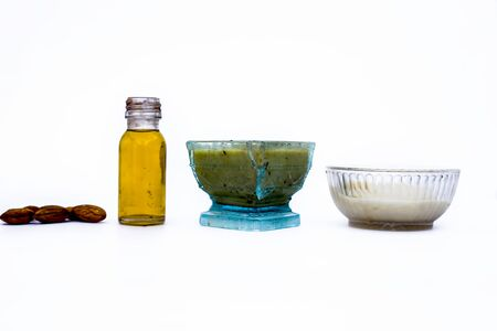 Home remedy to cure hair damage isolated on white i.e. almond oil along with egg white well mixed in a glass bowl and all the raw ingredients present on the surface.