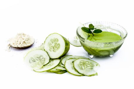 Cucumber face pack isolated on white i.e. Cucumber juice well mixed with gram flour in a glass bowl and all the raw ingredients present on the surface.Used for instant glow. Standard-Bild - 124568598
