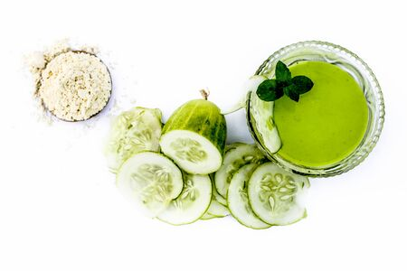 Cucumber face pack isolated on white i.e. Cucumber juice well mixed with gram flour in a glass bowl and all the raw ingredients present on the surface.Used for instant glow. Standard-Bild - 124568661