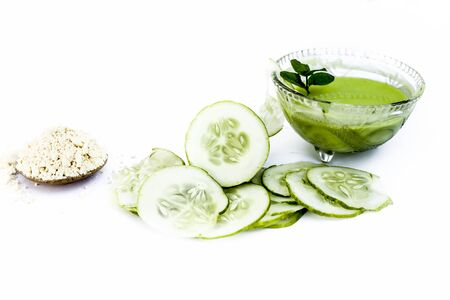 Cucumber face pack isolated on white i.e. Cucumber juice well mixed with gram flour in a glass bowl and all the raw ingredients present on the surface.Used for instant glow. Standard-Bild - 124568850