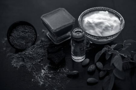 Organic hair conditioner on wooden surface i.e. Hing or devils dung and almond oil with yogurt in a glass bowl and all the raw ingredients present on the surface with some rose leaves.
