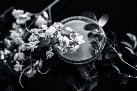 Ayurvedic herb Drumstick flowers along with some leaves on wooden surface along with its paste in a glass bowl.