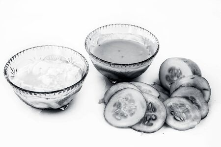 Cucumber face pack isolated on white i.e. Cucumber pulp well mixed with dahi or yogurt in a glass bowl and entire raw ingredients present on the surface.Used to cure acne prone skin.