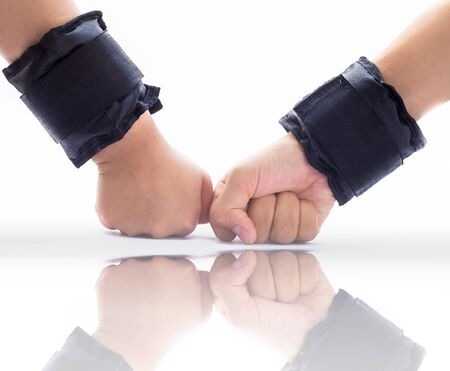 Two hands wearing black colored wrist weights or wrist bands isolated on white along with its reflection also. Stock Photo