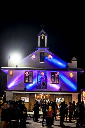 Church decorated with colorful lights during Christmas and a Christmas tree. Reklamní fotografie