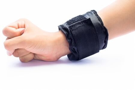 Close up of human hand wearing black colored wrist weight in his hand and doing exercise isolated on white.