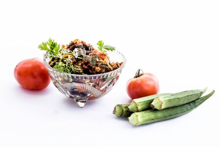 Popular Indian Lunch dish isolated on white i.e. Bhareli Bhindi or bareli bindi or fried crispy stuffed okra,with raw okra pods and tomatoes.