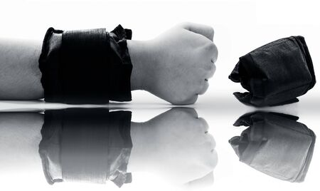 Single hand isolated on white wearing black colored wrist weight and another one on the surface with its reflection also.