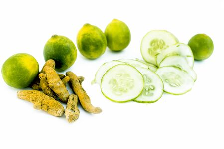 Cucumber face pack isolated on white i.e. Cucumber slices or cucumber pulp well mixed with turmeric powder and some lemon juice in a bowl and entire raw ingredients present on the surface.