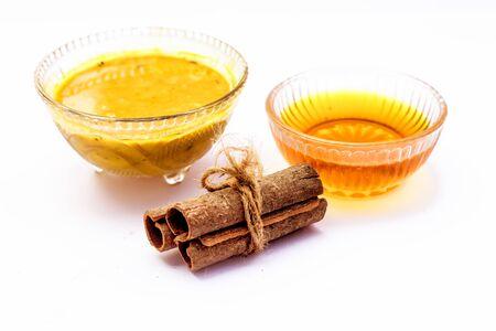 Pacchetto viso alla cannella isolato su bianco, ad esempio cannella o polvere di tej ben miscelata con miele in una ciotola di vetro e interi ingredienti grezzi presenti sulla superficie, utilizzato per pulire l'acne e le macchie dalla pelle. Archivio Fotografico