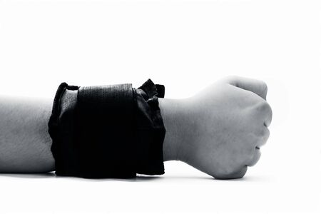 Close up of human hand wearing black colored wrist weights or wrist bands isolated on white. Stock Photo