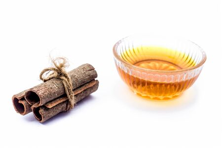 Cinnamon face pack isolated on white i.e. Cinnamon or tej powder well mixed with honey in a glass bowl and entire raw ingredients present on the surface,Used to clean acne and spots from skin.