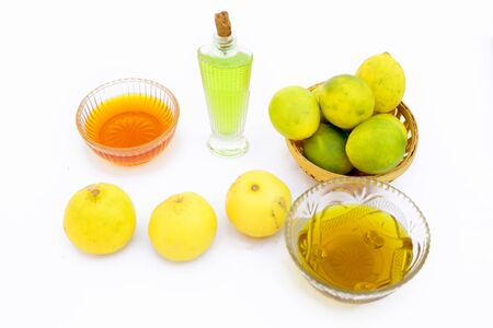Lemon hair growth mask isolated on white i.e. Lemon juice well mixed with honey and Olive oil in a glass bowl with entire raw ingredients.