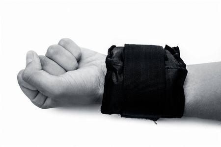 Single hand isolated on wearing black colored wrist weight or band in his hand.