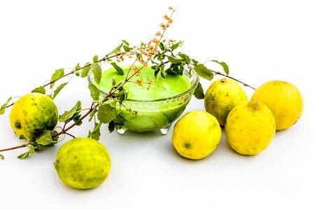 Lemon face pack isolated on white i.e. lime juice well mixed with tulsi or holy basils juice.Used for the treatment or to remove dirt,dust and other impurities. Фото со стока
