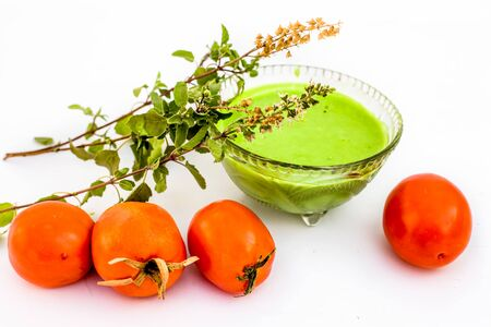 Tulsi face pack isolated on white i.e. Tomato puree or pulp well mixed with holy basil leaves juice.Used to remove acne and pimples gradually. Фото со стока