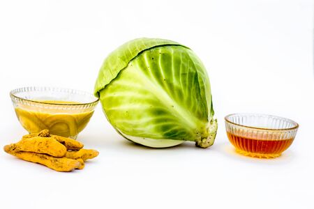 Cabbage face mask isolated on white consisting of cabbage juice well mixed with honey and turmeric in a glass bowl and entire raw ingredients present on the surface.Used to remove infections and tans. Фото со стока