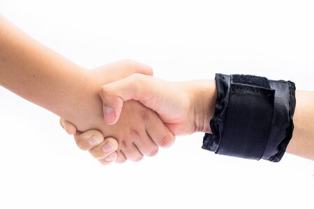 Male hand wearing black colored wrist weights and helping the other female hand isolated on white.Concept of togetherness and teamwork. Standard-Bild