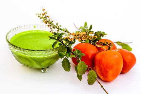 Tulsi face pack isolated on white i.e. Tomato puree or pulp well mixed with holy basil leaves juice.Used to remove acne and pimples gradually. Stock fotó