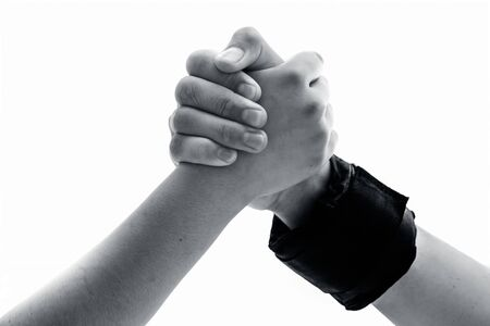 Male hand wearing black colored wrist weights and helping the other female hand isolated on white.Concept of togetherness and teamwork. Stock Photo