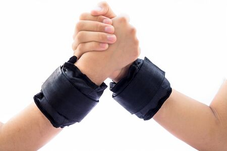 Close up of pair of hands one of male and the other one of female helping each other by supporting. Both of them wearing black colored wrist weights.