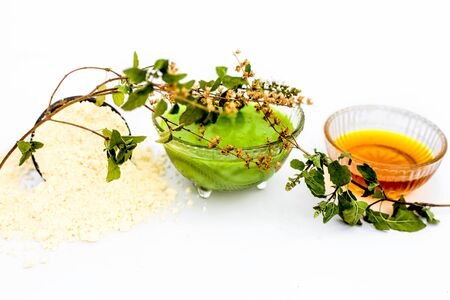Basil face mask isolated on white i.e. Basil leaves juice well mixed with honey and gram flour in a bowl and entire raw ingredients present on the surface.Used for instant acne and pimple free glow.