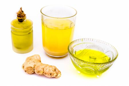 Cure to dandruff isolated on white i.e. Castor oil well mixed with ginger juice in a glass bowl along with entire raw ingredients.