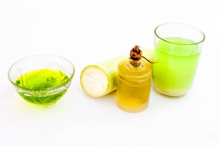 Hair remedy for Grey hair isolated on white i.e. Bottle gourd juice well mixed with olive oil in a glass cup and entire raw ingredients present on the surface.