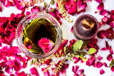 Face pack to clean sunburns and rashes isolated on white i.e Rose water well mixed with tulsi juice.Entire ingredients present on the surface. Stock Photo