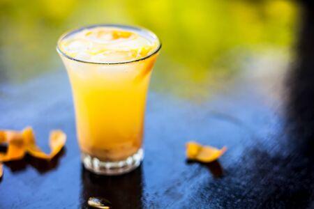 Popular Indian summer and Ramada drink on black shiny surface i.e. Chikoo falooda or chikoo shake or chikoo ka sherbat.