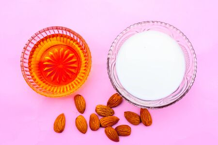 Milk and almond face pack on isolated on pink surface i.e. Raw milk,almond,honey well mixed in a glass bowl and used to Ex-foliate skin