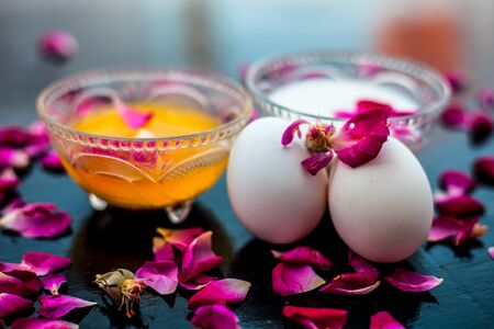 Anti-aging face pack i.e.  Milk and egg face pack in a glass bowl on shiny black surface with some rose petals and entire of its constituents with it.
