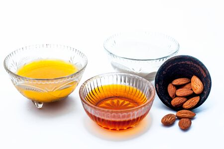 Natural ex-foliating face mask isolated on white in a glass bowl i.e. raw milk well mixed with honey, & almonds.Entire raw ingredients present on the surface.