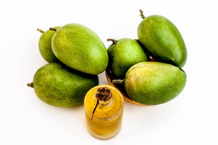 Raw organic green unripe mangoes isolated on white along with its extracted essential  oil.