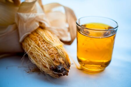 Raw organic fresh corn cob isolated on white along with its extracted fresh extract in a glass.