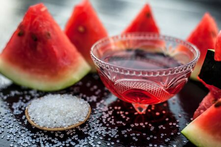 Best recipe ingredient to make homemade sugar scrub on wooden surface consisting of watermelon pulp well mixed with sugar in a glass bowl.
