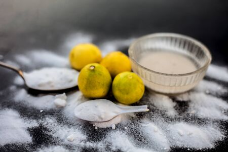Baking soda face mask in a glass bowl on wooden surface along with some baking soda sprinkled on the surface and lemons also on surface. Used to blemishes skin instantly. Imagens - 127582837