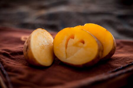Creative shot of Potatoes with a unique cut i.e. of Heart shape in it. Concept of health care and medical along with heart, cholesterol and weight-loss by avoiding the potatoes and its products. Imagens - 127582852