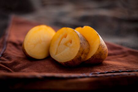 Creative shot of Potatoes with a unique cut i.e. of Heart shape in it. Concept of health care and medical along with heart, cholesterol and weight-loss by avoiding the potatoes and its products. Imagens - 127582675