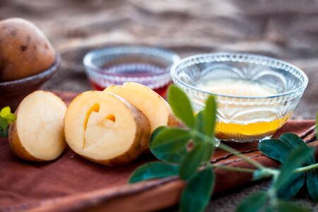 Potato juice face mask for skin whitening in a glass bowl on wooden surface along with raw potato and some organic honey in another bowl with a potato cut in heart shape.