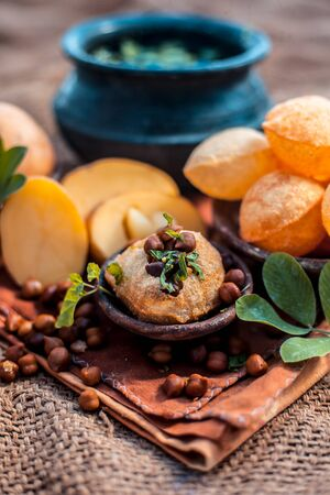 Famous Indian & Asian street food dish i.e. Panipuri snack in a clay bowl along with its flavored spicy water in another clay vessel. Entire consisting raw ingredients present on the surface. Imagens - 127582689