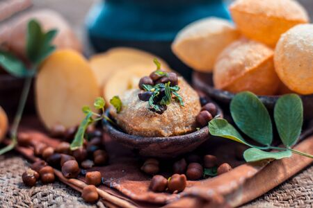 Famous Indian & Asian street food dish i.e. Panipuri snack in a clay bowl along with its flavored spicy water in another clay vessel. Entire consisting raw ingredients present on the surface. Imagens - 127582697