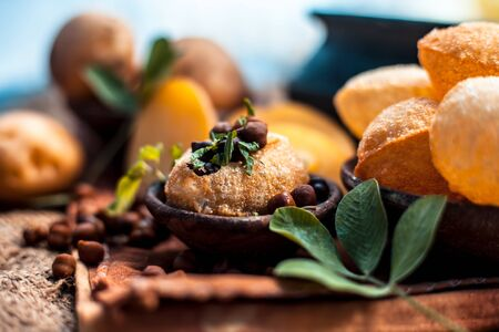 Famous Indian & Asian street food dish i.e. Panipuri snack in a clay bowl along with its flavored spicy water in another clay vessel. Entire consisting raw ingredients present on the surface. Imagens - 127582709