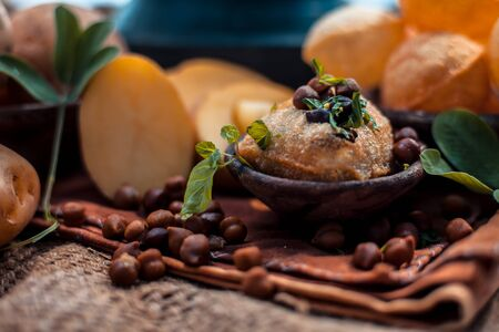 Famous Indian & Asian street food dish i.e. Panipuri snack in a clay bowl along with its flavored spicy water in another clay vessel. Entire consisting raw ingredients present on the surface. Imagens - 127582720