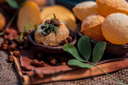 Famous Indian & Asian street food dish i.e. Panipuri snack in a clay bowl along with its flavored spicy water in another clay vessel. Entire consisting raw ingredients present on the surface. Imagens - 127582725
