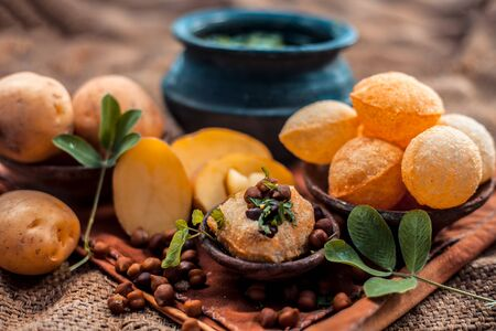 Famous Indian & Asian street food dish i.e. Panipuri snack in a clay bowl along with its flavored spicy water in another clay vessel. Entire consisting raw ingredients present on the surface.