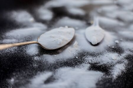Raw powdered baking soda in a antique spoon on wooden surface along with some more in a plastic spoon. Horizontal and top shot. Фото со стока